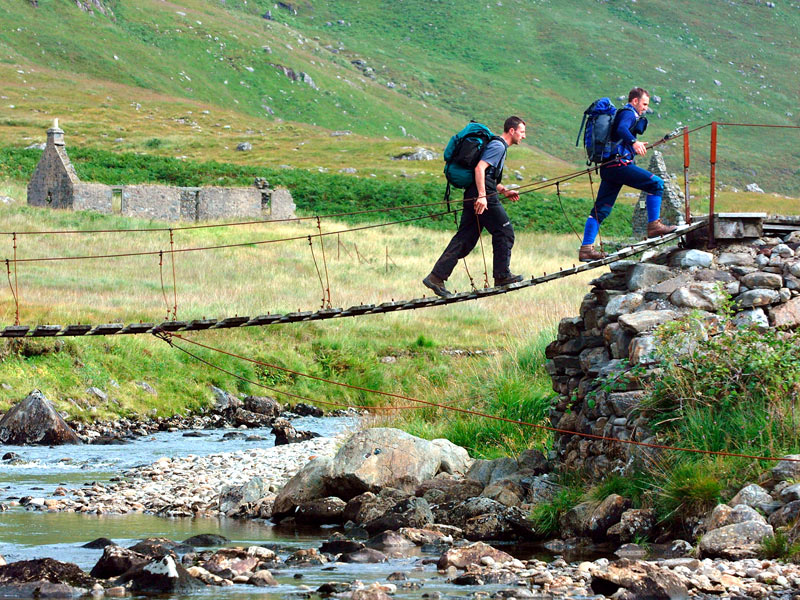 Walking across a ropey bridge in the West Highland Way