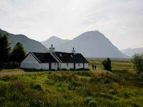 GLEN COE (GLENCOE) - BLACKROCK COTTAGE WITH THE MOUNTAIN OF BUACHAILLE ETIVE MOR IN THE DISTANCE.